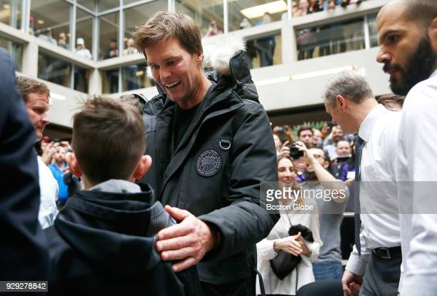 New England Patriots quarterback Tom Brady greets a child as he arrives to have his head shaved as part of Saving By Shaving 5 benefiting the...