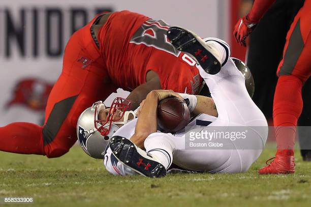 New England Patriots quarterback Tom Brady grimaces as he is sacked by Tampa Bay's Clinton McDonald in the first quarter The New England Patriots...