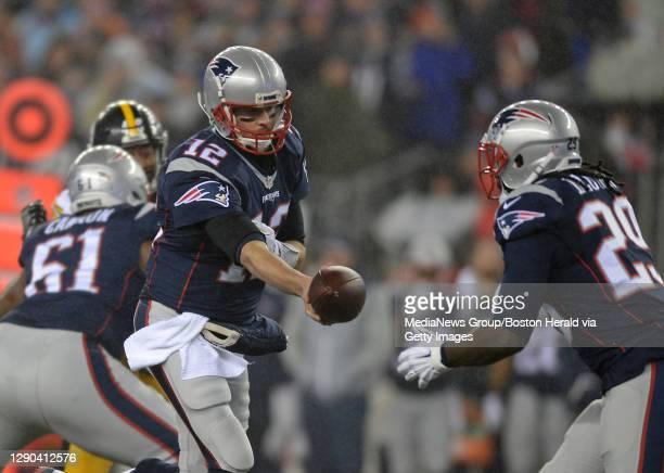 New England Patriots quarterback Tom Brady hands off the ball to New England Patriots running back LeGarrette Blount during the first quarter of the...