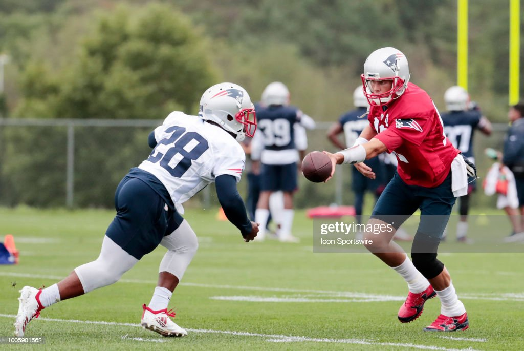 New England Patriots quarterback Tom Brady (12) hands off to New England Patriots running back James White (28) during Patriots Training Camp on July 26, 2018, at the Patriots Practice Facility at Gillette Stadium in Foxborough, Massachusetts.