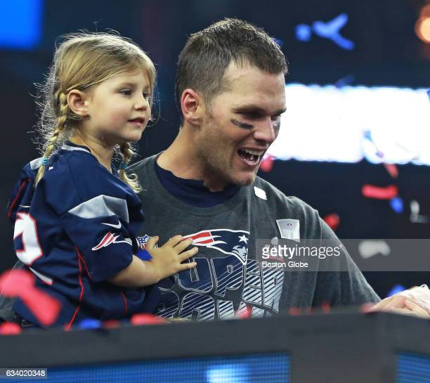 New England Patriots quarterback Tom Brady holds his daughter Vivian on the podium as he waits to speak following winning Super Bowl LI The Patriots...