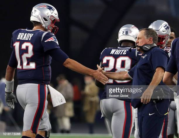 New England Patriots quarterback Tom Brady is congratulated by New England Patriots head coach Bill Belichick after throwing his first touchdown pass...