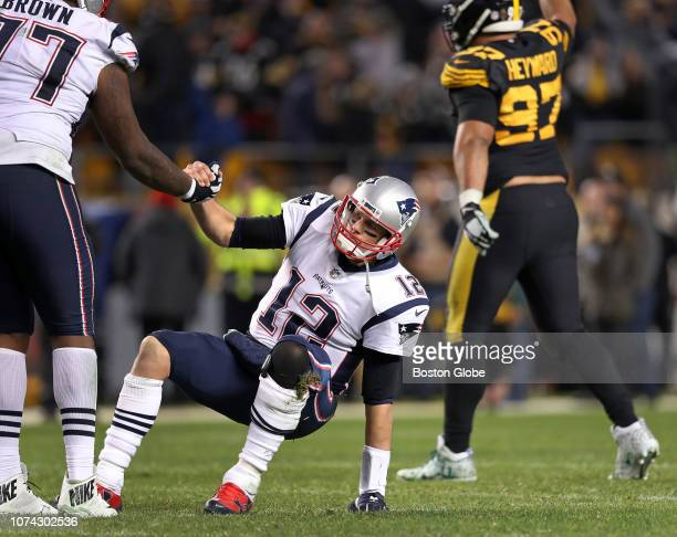 New England Patriots quarterback Tom Brady is helped up off the turf by teammate Trent Brown after his last pass of the game fell incomplete in the...