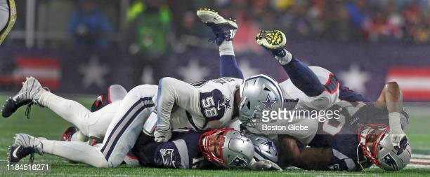 New England Patriots quarterback Tom Brady is tackled by Dallas Cowboys defensive end Robert Quinn as well as one of his own offensive linemen...
