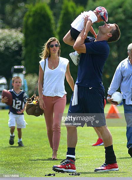 New England Patriots quarterback Tom Brady kisses his son Benjamin as his other son John left walks with Brady's wife Gisele Bundchen at the end of...