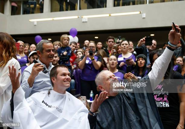 New England Patriots quarterback Tom Brady left and Massachusetts Governor Charlie Baker pose for a selfie as they get their heads shaved as part of...