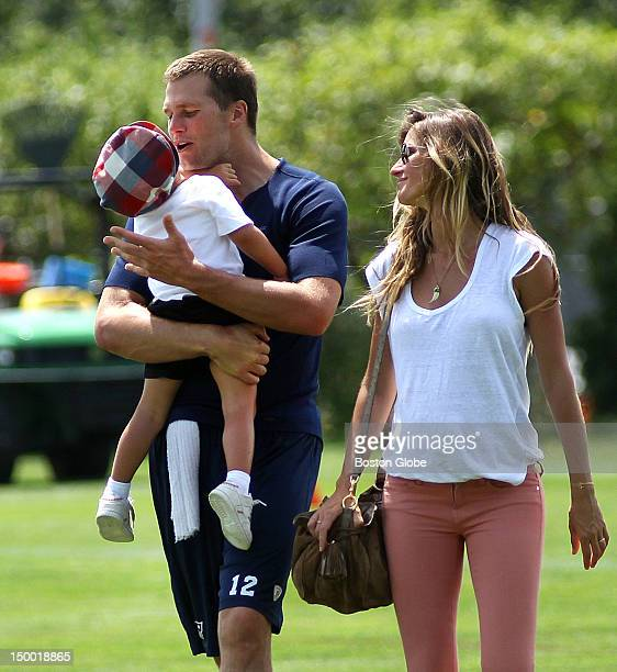 New England Patriots quarterback Tom Brady left carries his son Benjamin as he walks off the practice field with wife Gisele Bundchen right at the...