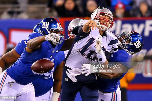 New England Patriots quarterback Tom Brady loses the football after he gets hit by New York Giants defensive end Robert Ayers and New York Giants...