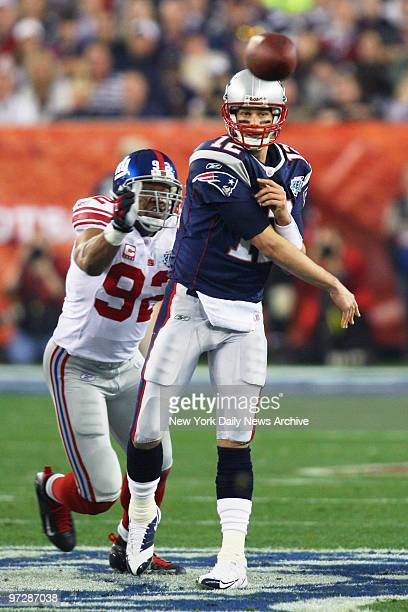 New England Patriots' quarterback Tom Brady passes the ball under pressure from New York Giants' defensive end Michael Strahan during the first...