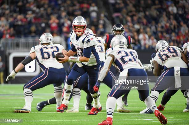 New England Patriots quarterback Tom Brady prepares to hand off to New England Patriots running back James White during the football game between the...