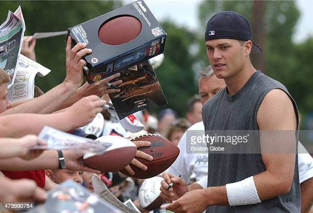 New England Patriots quarterback Tom Brady signs autograph for his fans after a practice during the Patriots training camp at Bryant College in...