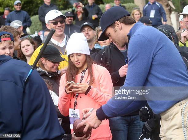 New England Patriots quarterback Tom Brady signs autographs during the third round of the ATT Pebble Beach National ProAm at the Pebble Beach Golf...