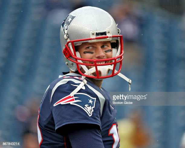 New England Patriots quarterback Tom Brady smiles to some young fans on the sidelines before they play the San Diego Chargers at Gillette Stadium in...