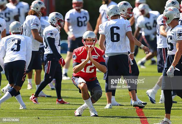 New England Patriots quarterback Tom Brady stretches during the first day of training camp at the practice fields at Gillette Stadium in Foxborough,...