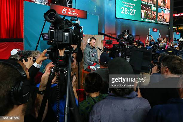New England Patriots quarterback Tom Brady surrounded by the media as he answers questions during Super Bowl Opening Night on January 30 at Minute...