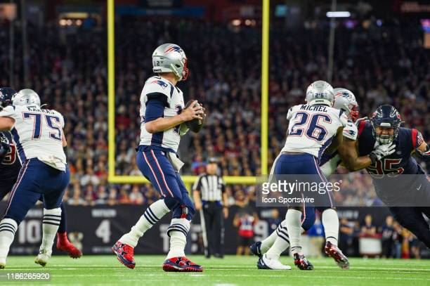 New England Patriots quarterback Tom Brady surveys the field with a clean pocket during the football game between the New England Patriots and...