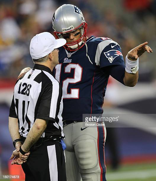 New England Patriots quarterback Tom Brady talks to a referee on the field during the first quarter of a preseason exhibition game against the New...
