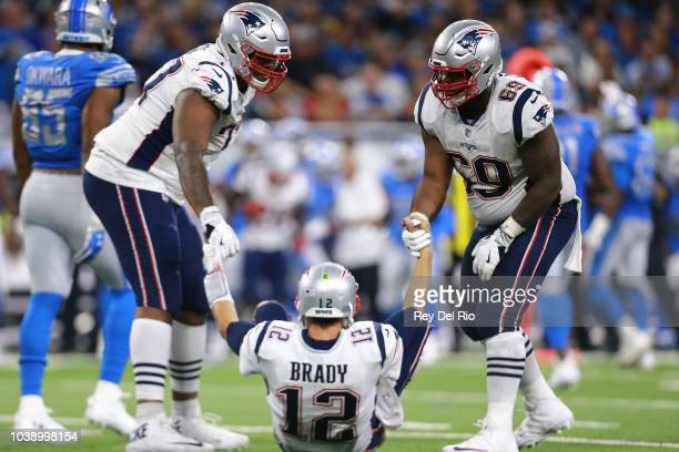 New England Patriots quarterback Tom Brady talks to teammates during the first half of an NFL football game against the Detroit Lions in Detroit...