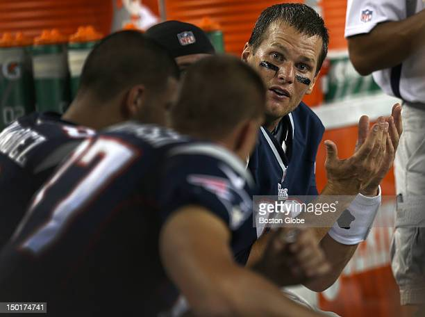 New England Patriots quarterback Tom Brady talks with his receivers on the bench during the first quarter of a preseason exhibition game against the...