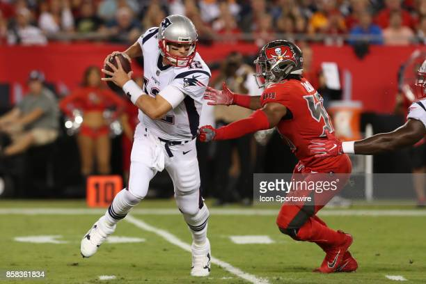 New England Patriots quarterback Tom Brady tries to avoid being sacked by Tampa Bay Buccaneers outside linebacker Devante Bond during the NFL game...