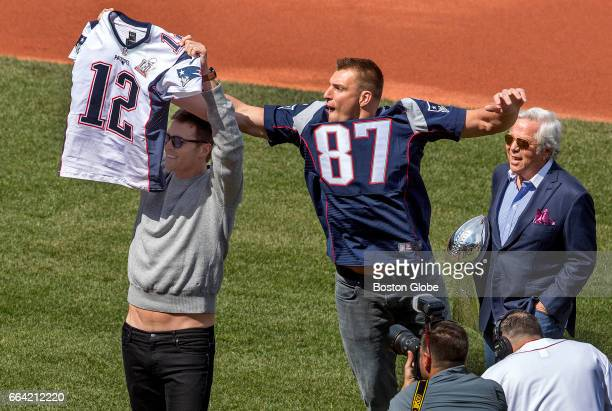 New England Patriots' Rob Gronkowski reaches to steal a jersey from teammate Tom Brady during pregame ceremonies on Opening Day at Fenway Park in...
