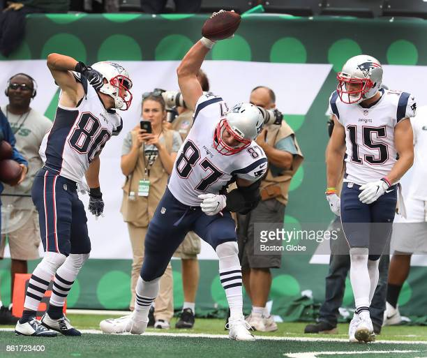 New England Patriots' Rob Gronkowski spikes the ball after a touchdown reception with approval from teammates Danny Amendola left and Chris Hogan...
