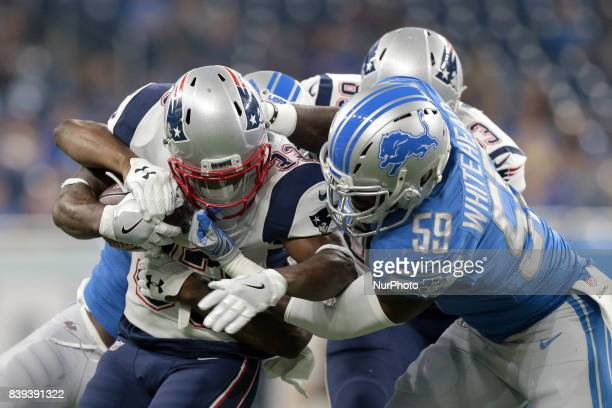 New England Patriots running back Dion Lewis is tackled by Detroit Lions linebacker Jarrad Davis and middle linebacker Tahir Whitehead during the...