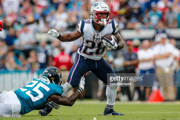 New England Patriots running back James White attempts to escape a tackle by Jacksonville Jaguars cornerback D.J. Hayden during the game between the...