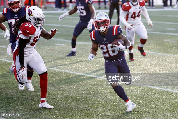 New England Patriots running back James White carries the ball as Arizona Cardinals linebacker De'Vondre Campbell moves in during a game between the...