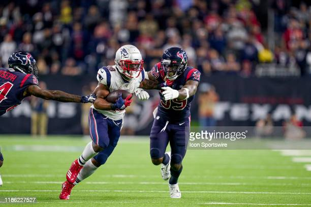 New England Patriots running back James White fends off Houston Texans free safety Tashaun Gipson during the game between the New England Patriots...