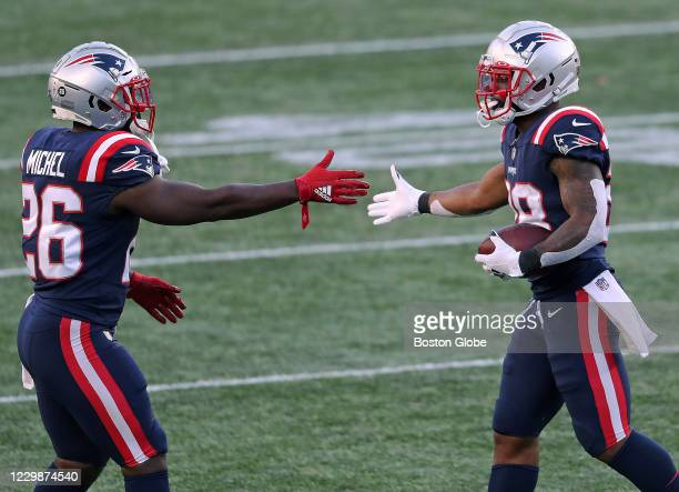 New England Patriots running back James White gets a hand from teammate Sony Michel after White scored his second rushing touchdown of the game in...