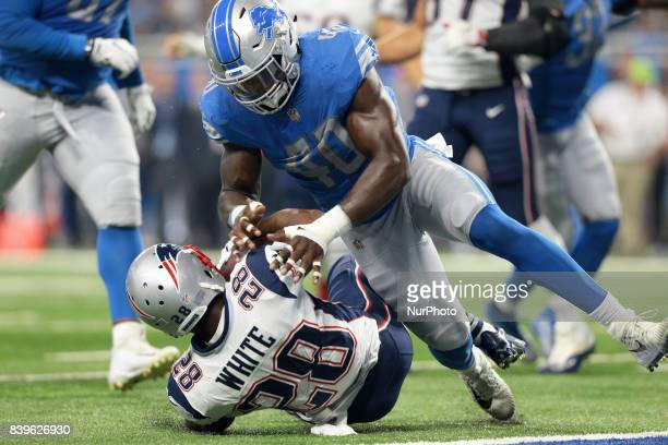 New England Patriots running back James White gets tacled by Detroit Lions linebacker Jarrad Davis during the first half of an NFL football game in...