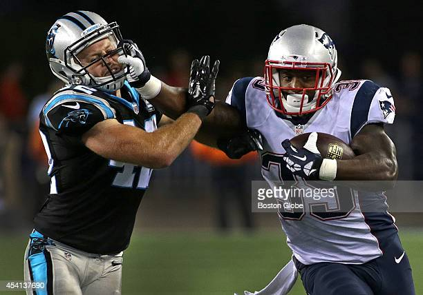 New England Patriots running back Jonas Gray fends off a tackle by Carolina Panthers strong safety Roman Harper on this carry in the fourth quarter...