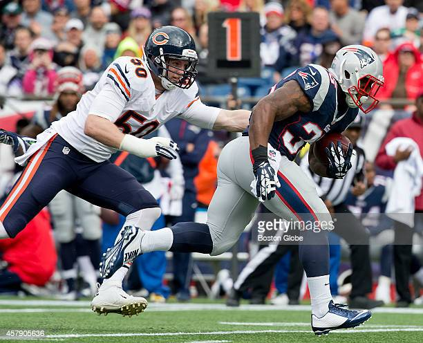 New England Patriots running back Jonas Gray runs past Chicago Bears linebacker Darryl Sharpton en route to a 19yard run during first quarter action...