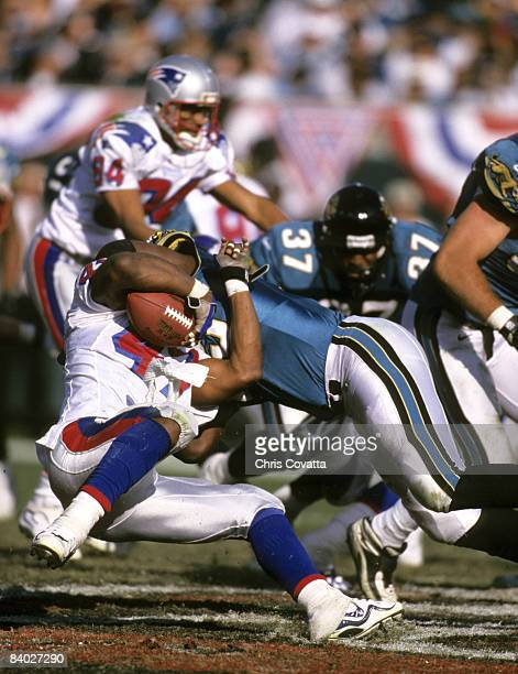 New England Patriots running back Robert Edwards is hit hard and tackled by Jaguars defensive end Eric Curry during the Patriots 2510 loss to the...