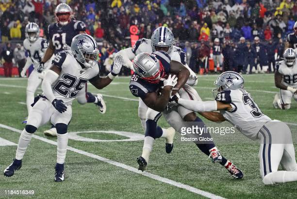 New England Patriots running back Sony Michel is tackled by Dallas Cowboys players Xavier Woods, , Joe Thomas, and Byron Jones during the fourth...