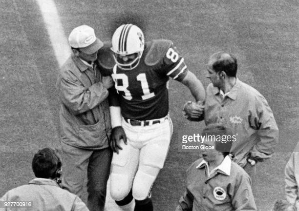 New England Patriots Russ Francis is escorted off the field after being injured during a game during a game against the Buffalo Bills at Rich Stadium...