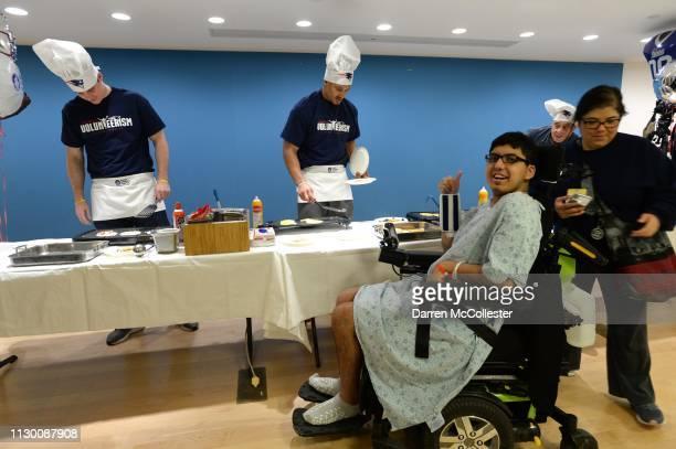 New England Patriot's Ryan Izzo and Derek Rivers flip pancakes for Frankie at Boston Children's Hospital March 12, 2019 in Boston, Massachusetts.