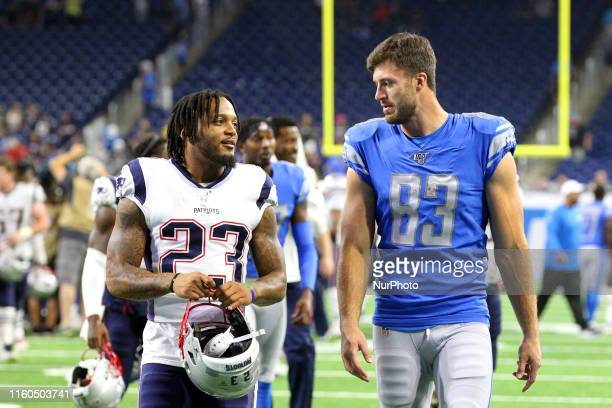 New England Patriots safety Patrick Chung walks off the field with Detroit Lions tight end Jesse James after an NFL football game against the Detroit...
