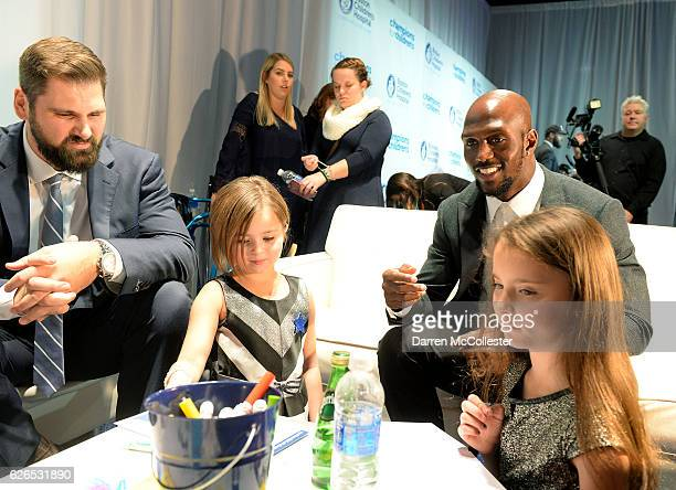 New England Patriots Sebastian Vollmer and Devin McCourty hang out with Isabel and Elia at Champions for Children's at Seaport World Trade Center on...
