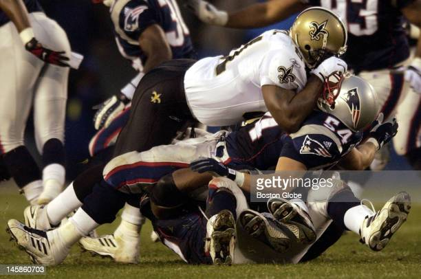 New England Patriots Tedy Bruschi is sandwiched as he gets in on the tackle of New Orleans Saints running back R Williams during the first half of...