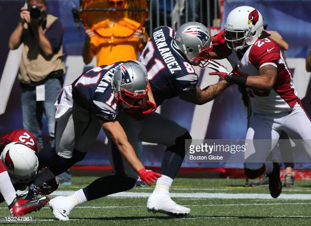 New England Patriots tight end Aaron Hernandez appears to catch his right foot in the turf as New England Patriots wide receiver Julian Edelman falls...