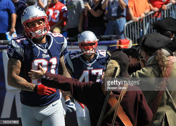 New England Patriots tight end Aaron Hernandez gets a hand from a Patriot Minuteman on the field as he prepares for pregame warmups before the New...