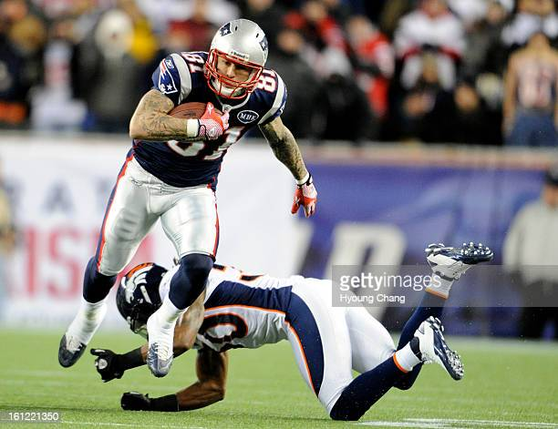 New England Patriots tight end Aaron Hernandez gets away from a missed tackle bu Denver Broncos free safety David Bruton on the first drive of the...