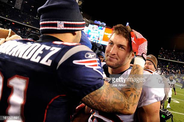 New England Patriots tight end Aaron Hernandez pats a smiling Denver Broncos quarterback Tim Tebow after their beating the Broncos 4510 in their AFC...