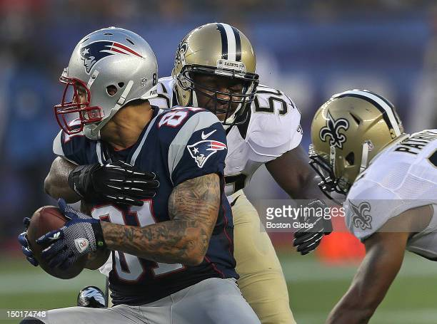 New England Patriots tight end Aaron Hernandez pulls in a pass reception as New Orleans Saints linebacker Curtis Lofton closes in during the first...