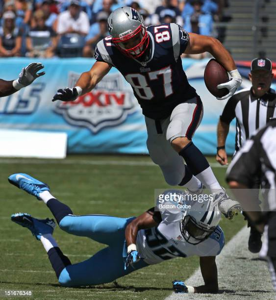 New England Patriots tight end Rob Gronkowski hurdles a tackle by Tennessee Titans defensive back Robert Johnson for a 28-yard catch and run on a...