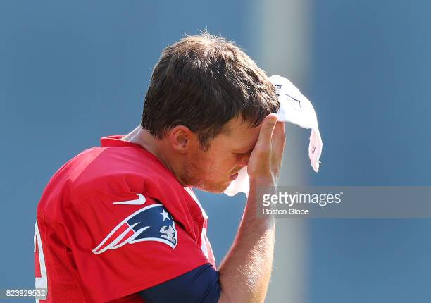 New England Patriots Tom Brady wipes the sweat from his face during the second day of training camp at the Gillette Stadium practice field in...
