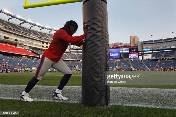New England Patriots wide receiver Donte' Stallworth uses an end zone goal post as he stretches before a preseason exhibition game against the New...