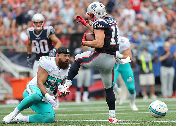 f2144def7e6 New England Patriots wide receiver Julian Edelman and a helmetless Miami  Dolphins linebacker Koa Misi are